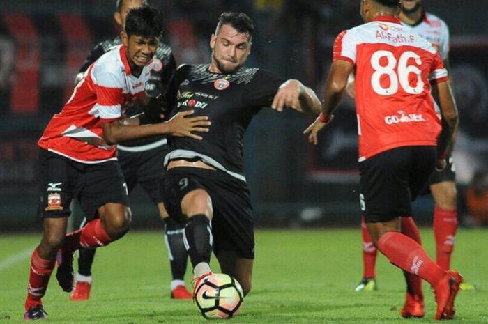 Marco Simic berduel dengan pemain Madura United